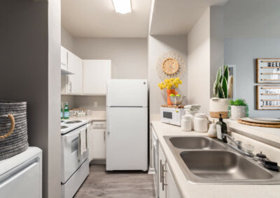 Kitchen With a Sink and a Refrigerator of an Apartment at Cadence at Southern University