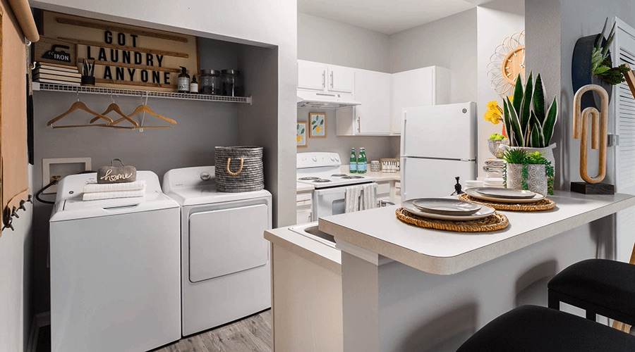 Bright kitchen with bar seating and adjacent laundry closet.